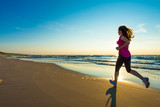 Teenage girl running, jumping on beach
