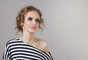 Portrait of a beautiful young woman in a striped shirt.