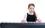 Smiling schoolgirl plays on the electric piano.