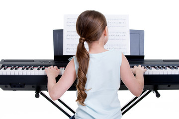 Back view of a little girl playing the electric piano.