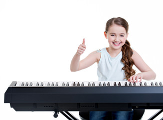 Smiling girl plays on the electric piano.