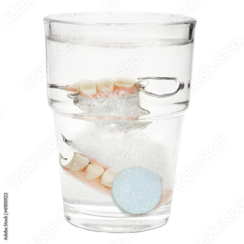 "False Teeth in a glass with cleaning tablets and water glass ""is"