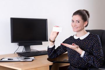 beautiful business woman showing visiting card in office and pc