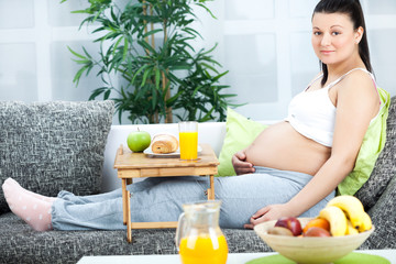 smiling young pregnant woman lying on the sofa