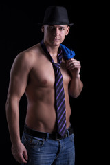 a muscular sexy man posing in a tie with a hat,on black backgrou