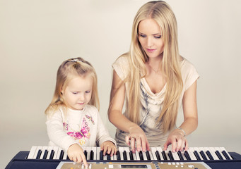 little cute girl with her mom playing on synthesizer