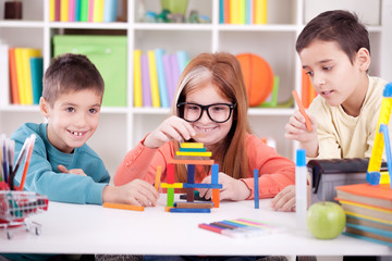 older sister and two younger brothers  play with wooden blocks a