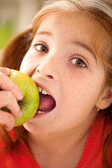 Cute little girl eating an apple