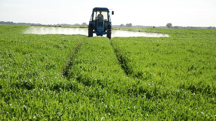 Tractor spray fertilize field with pesticide chemicals