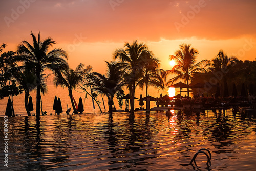 Sunset over swimming pool at a tropical resort
