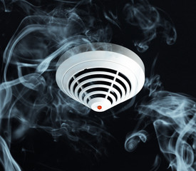 Smoke around fire detector on black background.