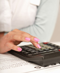 Businesswoman doing some paperwork using a calculator