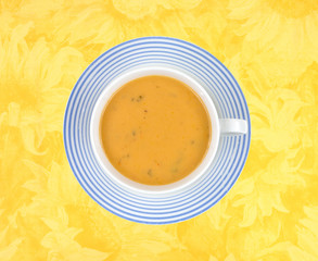 Gouda cheese soup in cup on floral cloth