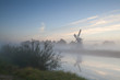 windmill by river in morning fog