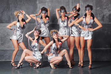 Group of seven happy cute girls in silver go-go costume ready to
