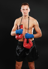 Young handsome boxer man isolated on black background.