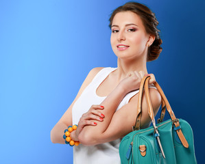The fashionable young woman holding bag.