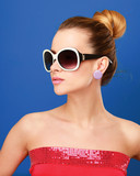 female with sunglasses, isolated on blue background.
