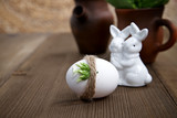 Easter egg against of ceramic rabbits in background