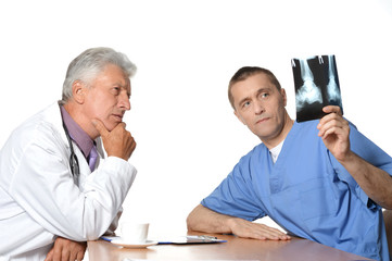 doctors looking at x-ray on a white