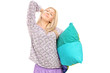Young woman in pajamas holding pillow and stretching herself