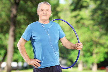 Smiling mature man with headphones holding a hula hoop in park