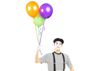 Young mime artist holding balloons and looking at camera
