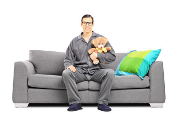 Young man in pajamas sitting on sofa with teddy bear