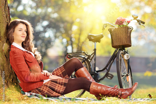 Young beautiful female with bicycle relaxing in park