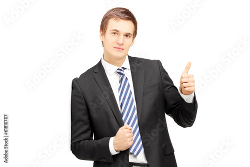 Young businessman in formalwear leaning against wall