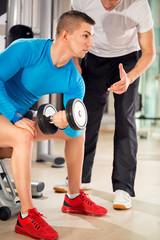 man exercising under supervision trainer