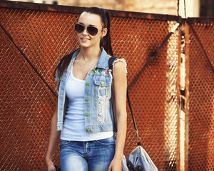 Beautiful girl in a denim jacket, sunglasses and a bag
