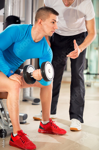 man exercising under supervision trainer