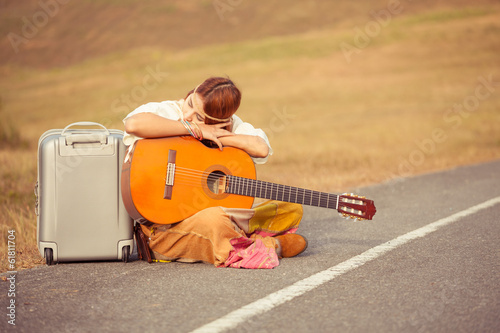 Hippie woman sitting on a countryside road