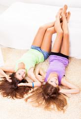 Two Beautiful teenage girls lying on the carpet