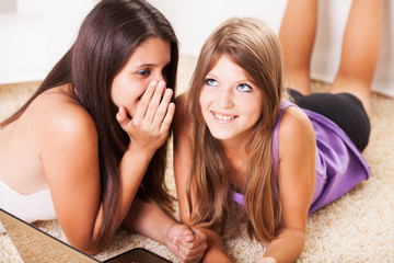 Two cheerful teenage girl Friends whisper secrets.