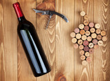 Red wine bottle, corkscrew and grape shaped corks