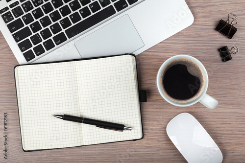 Notepad, laptop and coffee cup on wood table