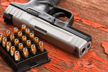 Close up of a handgun and rack of ammunition