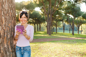 Smile brunette woman reading her ebook outdoor