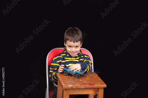 little boy playing indoor with model car