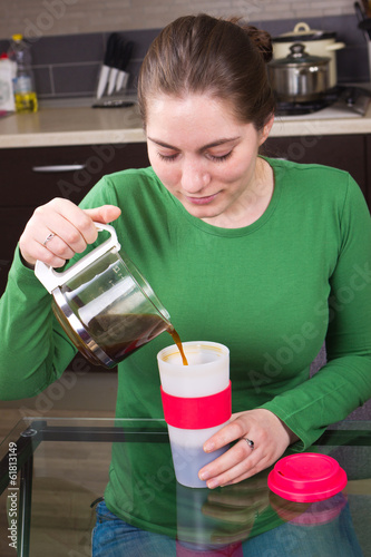 Young girl drinking coffee in kitchen