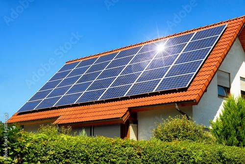 Leinwanddruck Bild Solardach auf einem Einfamilienhaus reflektiert die Sonne