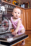 Child 1 year old in the kitchen at dishwasher