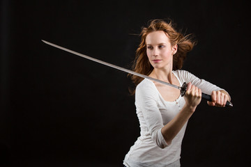 Beautiful woman in white shirt with a sword