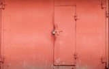 Red metal garage wall with locked gate. Background texture