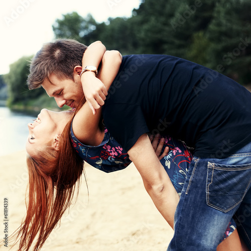 Beautiful cute couple on the beach near the water hugging