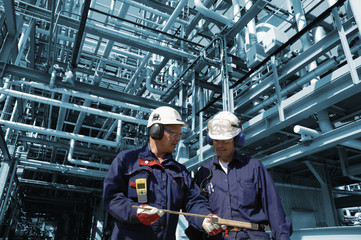 oil workers inside large refinery industry