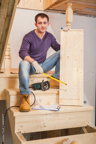a young worker sitting on ladder and holding one step