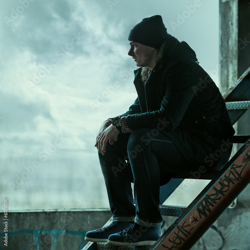 Trendy man sitting on the stairs and looks into the distance